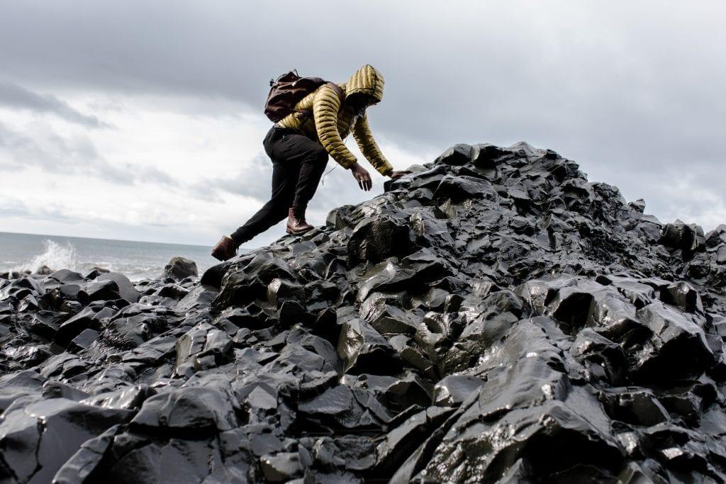 man-wearing-hoodie-and-black-pants-climbing-up-pile-of-rocks-1058958