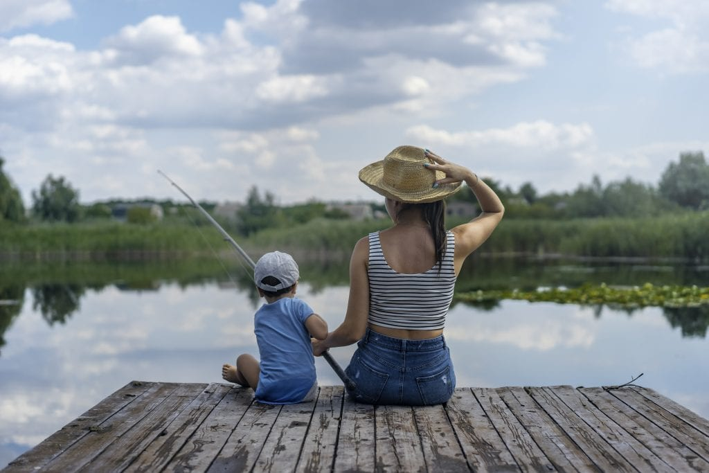 woman-and-boy-sitting-on-dock-holding-fishing-rod-2702625