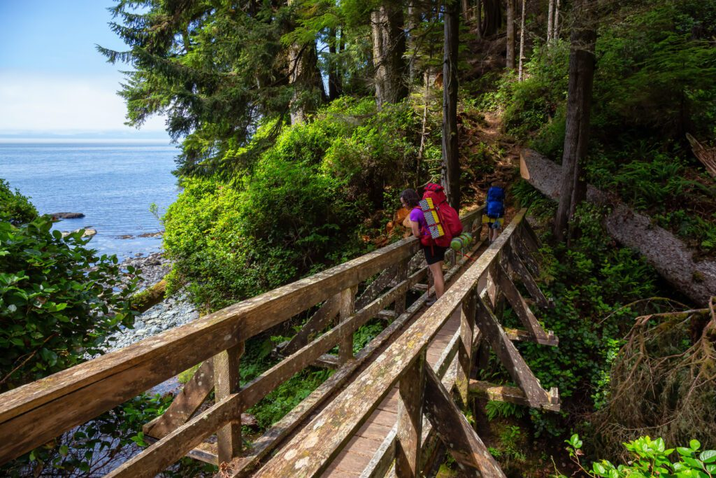 Adventurous female is hiking Juan de Fuca Trail on the Pacific Ocean Coast during a sunny summer day. Taken near Port Renfrew, Vancouver Island, BC, Canada