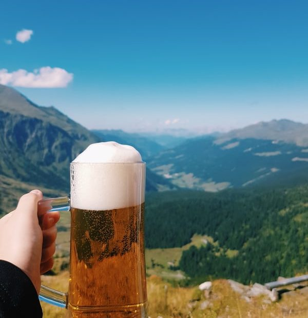 A girl holding a mug of beer in the cold, hilly region