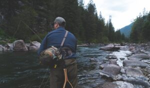 A guy doing fishing in a stream or small river tribune