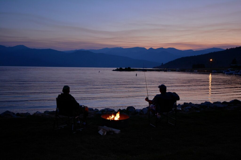 Two men enjoying fishing by the fire and river at dusk