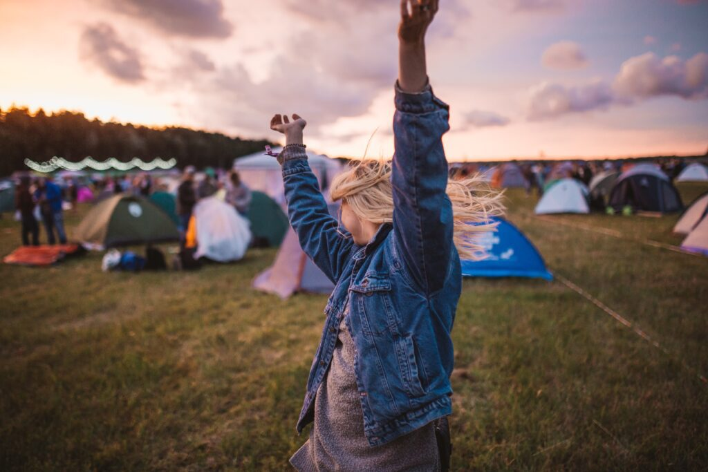 A girl walking through the tents on a campground